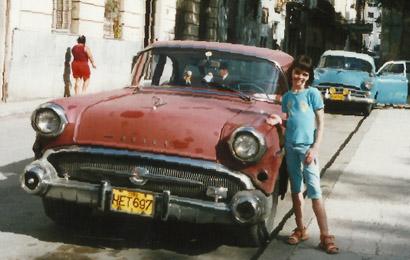 dziecko stojące przy czerwonym, starym samochodzie