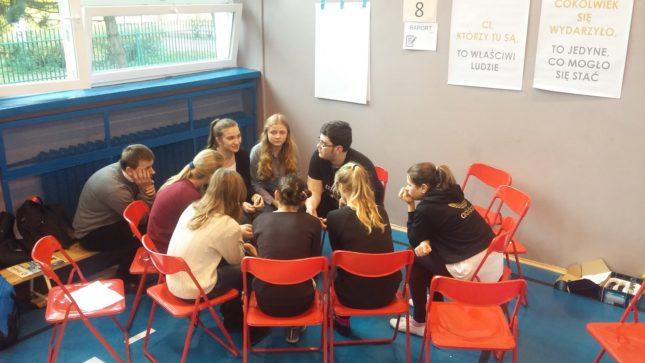 Grupa młodych ludzi rozmawiających i siedzących obok siebie na krzesłach
