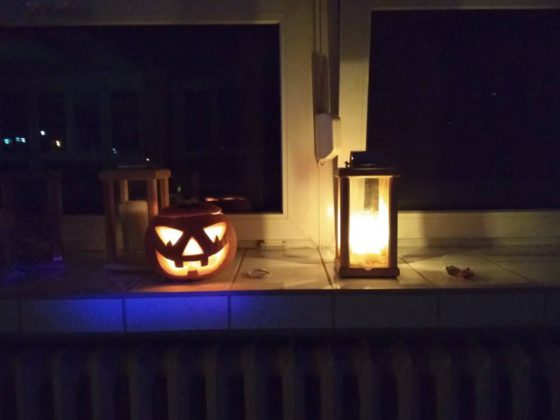dynia na halloween wraz z lampionem stoją na stole